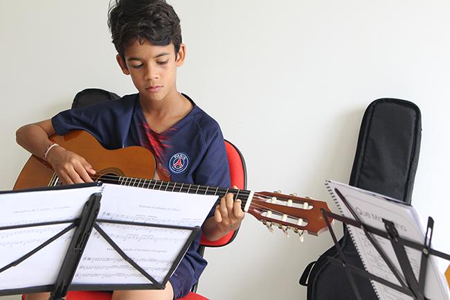 criança concentrada tocando violão