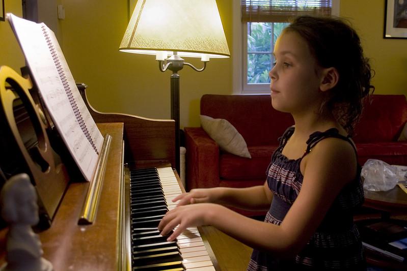 criança concentrada tocando piano